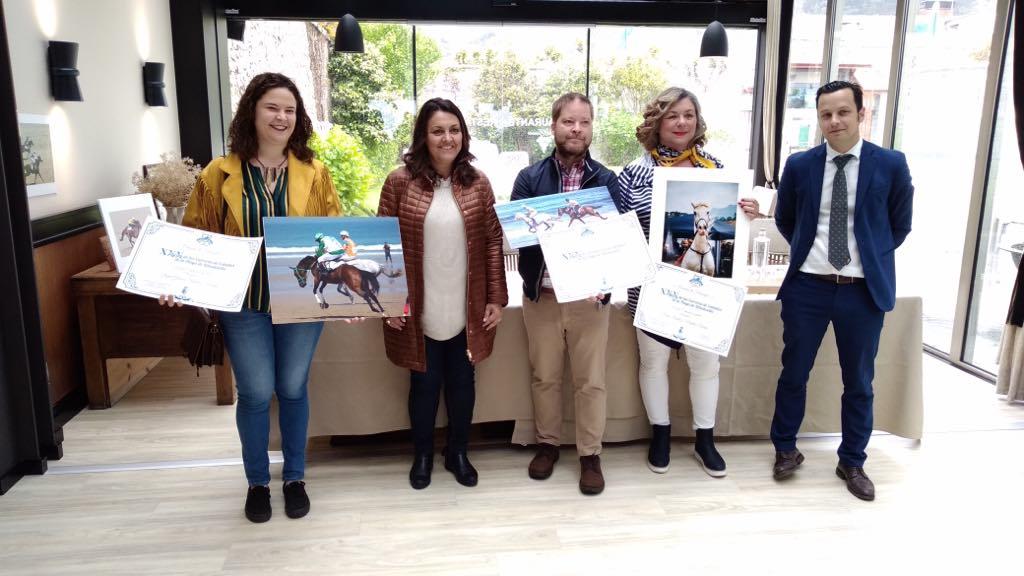 Carlos Dickman recoge el premio que le acredita como ganador del concurso fotográfico de las Carreras de Caballos de Ribadesella