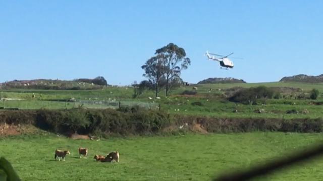 El helicóptero de la Guardia Civil toma tierra en Poo de Llanes para dar el alto a un caminante