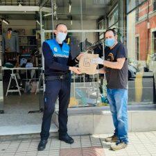 Piloña reparte mascarillas entre los comercios que están levantando sus persianas y abriendo sus puertas