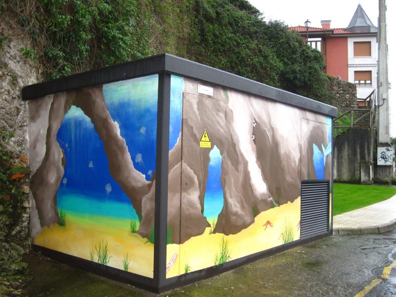 Un artista callejero redecora un trampantojo de Ribadesella que había sido víctima de los graffiteros