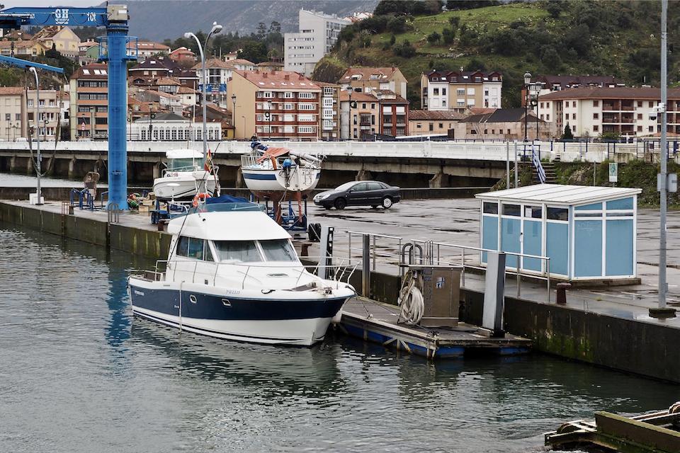 Un equipo de submarinistas saca a flote el barco sumergido en el puerto deportivo de Ribadesella
